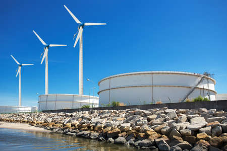 rafinery: Large natural gas storage tanks with a windmill.
