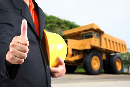 indenture: engineer hand holding yellow helmet for workers security against the background a large coal trucks