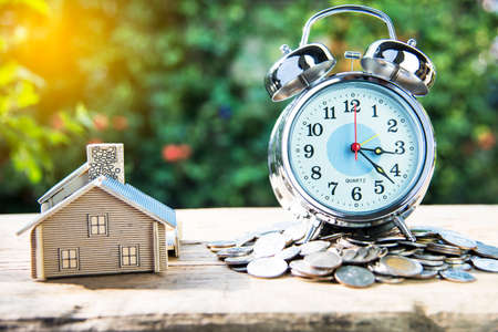alarm clock on a pile of coins and house placed