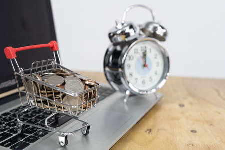 Coin in a trolley on a laptop keyboard and alarm clock. Ideas about online shopping, online shopping is a form of electronic commerce that allows consumers to directly buy goods from a seller over the internet.