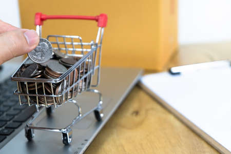 Men's Hand Picking Coins in a trolley on a laptop keyboard and contract. Ideas about online shopping