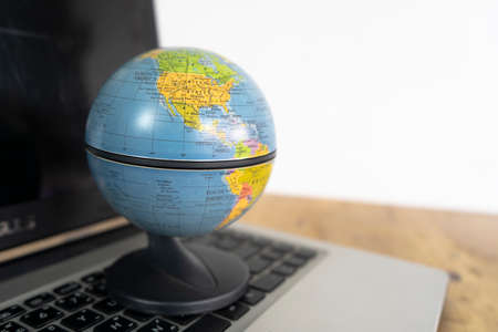 Globe on a laptop keyboard. Ideas about online network, online shopping is a form of electronic commerce that allows consumers to directly buy goods from a seller over the internet.