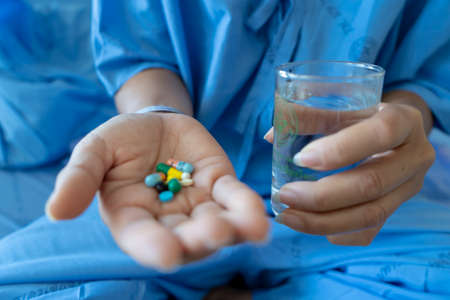 Blue dress woman on hospital bed Have medicine on hand and water