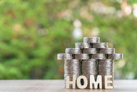 coin stack with house model, home message, savings plans for housing ,green background, financial concept