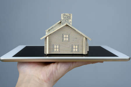 Model houses are placed on tablets that are in the hands of men. 版權商用圖片