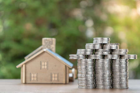 coin stack with house model, savings plans for housing ,green background, financial concept