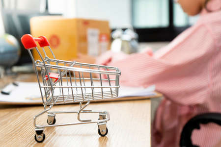 Online shopping concept. Shopping cart, Woman wrapping product in box, woman opening the package 版權商用圖片