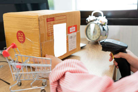 ecommerce concept, Online shopping concept. Woman wearing red shirt in office or home working prepare product in the box for send to customer who order by online. box for logistic with barcode scanner