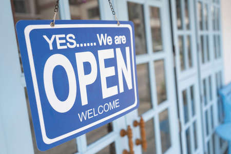 yes we're open sign on the blue doors in store. welcome sign at the store