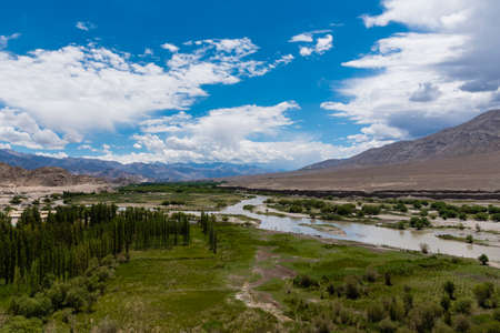 eventually: Indus river flowing through plains in Ladakh, India, Asia. Immediate surrounding of the stream is green, which eventually gives way to barren land