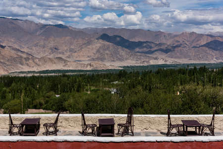 Table and chairs laid out on terrace ; with a vast view of landscape of Ladakh. Green trees and Himalayan mountains in the background.