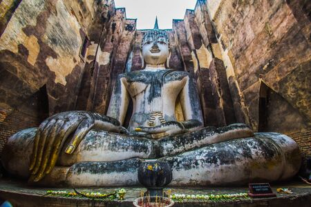 Sukhothai Historical Park  Thailand  traveller with ancient Buddha statue at Wat Si Chum temple. Imagens
