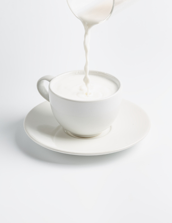 to maintain: fresh milk is poured from a glass into a cup isolated on white background