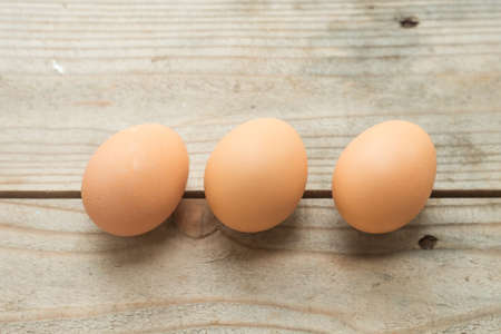 three eggs on wooden table photo