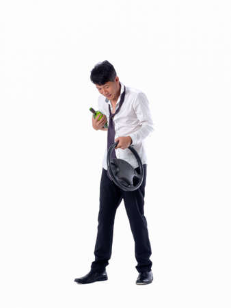 drunk business man wear black suit holding wine bottle and steering wheel on  isolated white background 写真素材