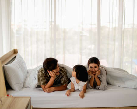 happy family having fun in bed room concept. father,mother and daugther smiling face, kiss love together lying on bed with duvet cover them copy space.