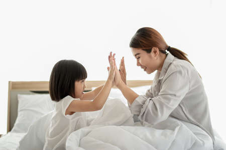 happy family in bed room concept.Young asia mother playing patty cake with her daughter sitting on bed in childrens room and smiling Imagens