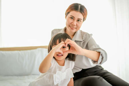 happy family in bed room concept. mother and daugther make heart symbol by hands comfortable bed.