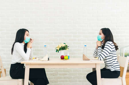 Two beautiful Asian women are sitting and eating apart social distancing concept new normal lifestyle Standard-Bild