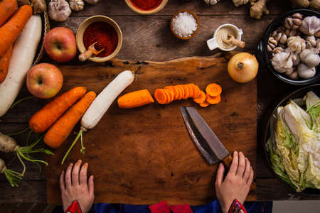 Hand holding knife and slice kimchi cabbage on wooden cutting board for cooking, Korean food