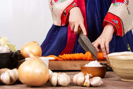 close up hand woman wearing hanbok cutting vegetable with knife on table preparing cook kimchi traditional food in kitchen copy space
