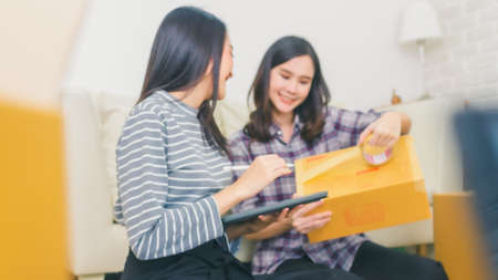 Beautiful young asian and friend happy holding tree from boxes.Young Asian women working with box for packaging order from shopping online in home,Own Business Start up