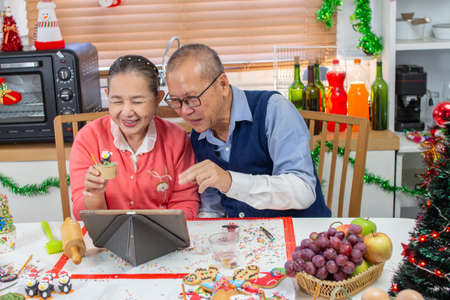 Senior An Asian grandfather and grandmother wearing aprons learning to make cupcake online with a tablet having fun in a kitchen.
