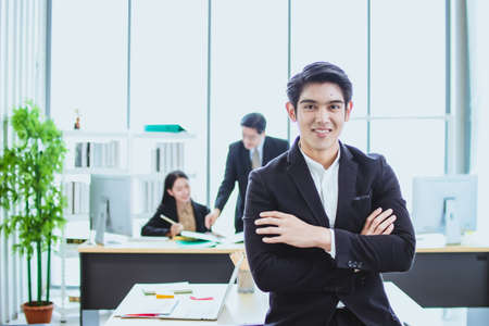 young asian business man. smile face. sitting and standing in office. talk business. phone call with official working background. looking camera cross arm copy space