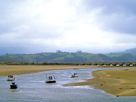 Boats on a estuary on a cloudy day in Cantabria, Spain Stock Photo