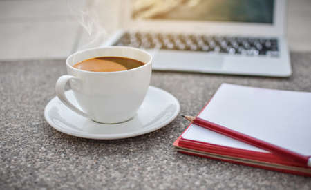 defocus coffee cup on ground with notebook and laptop,morning,hot coffee