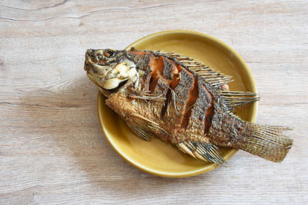 fried fish on brown ceramic plate and wooden backgrounds,spot focus,copy space Stok Fotoğraf