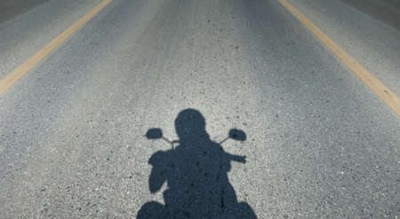 Shadow of motorcycle driving the road, copy space