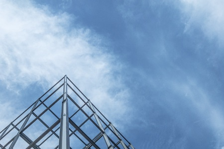 Construction of building steel structure on sky background.