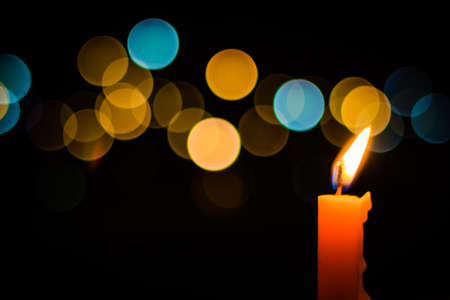 One candle flame light at night with bokeh on dark background