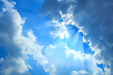 Blue sky with white clouds . Sunbeam Shine through the cloud on the blue sky