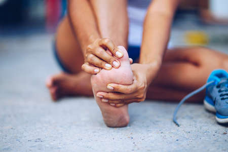 Young woman massaging her painful foot from exercising and running Stock fotó