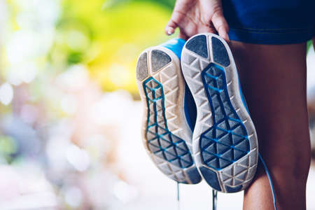 woman holding Sports shoes in hand