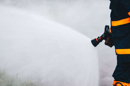 Firefighter using extinguisher and water from hose for fire fighting, Firefighter spraying high pressure water to fire with copy space.