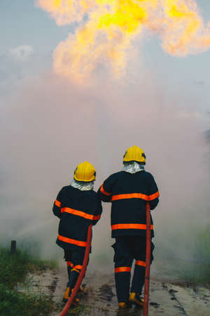 Firefighter spraying high pressure water to fire with copy space. Stock fotó