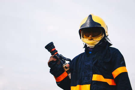 firefighter holding fire hoses in uniform and oxygen mask