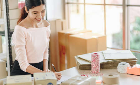 Asian woman writing clipboard, home delivery, SME e-commerce concept
