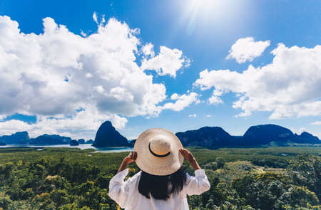 Asian woman traveler wearing a white shirt holding hat and looking at Samed Nang Chee amazing mountains and forest, travel holiday relaxation concept. Stock fotó
