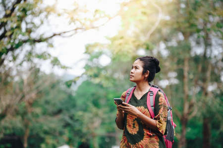 Traveler backpacker asian women use smartphone with nature background , concept travel , copy space Stock fotó