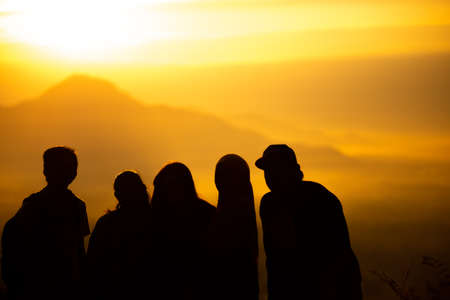 Silhouette traveler group at sunset time on background mountains