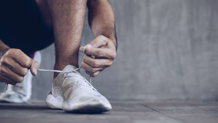 Male athlete tying shoelaces getting ready for exercise, banner background with copy space Stock fotó