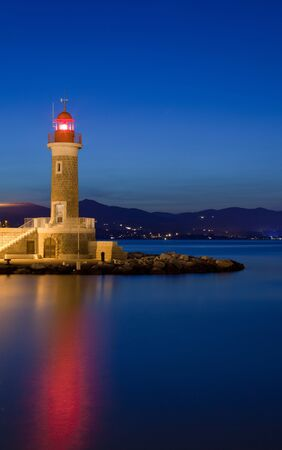 Lighthouse mountain sunset sea night city Archivio Fotografico - 129456105