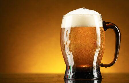Taza de vidrio de espuma de cerveza de color oscuro sobre un fondo marrón Foto de archivo