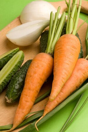 Vegetables carrot cucumbers onion green background
