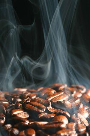 Les grains de café rôtissent la vapeur de fumée sur fond noir Banque d'images