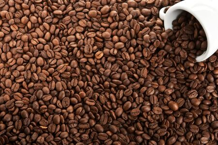 Coffee beans scattered white cup . Stok Fotoğraf